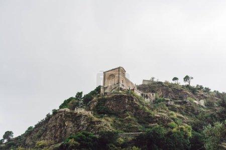 Foto de Savoca, Italia - 3 de octubre de 2019: Vista baja de la iglesia de san nicolo en la colina cerca de árboles verdes contra el cielo con nubes. - Imagen libre de derechos