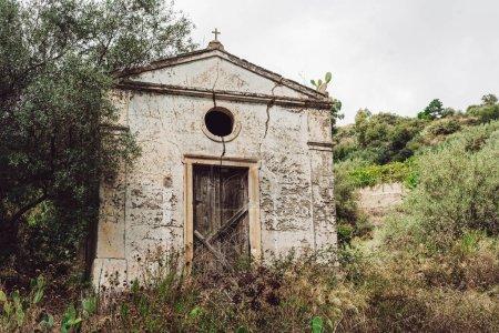Photo pour Ancien bâtiment à proximité d'arbres et de buissons verts en italique - image libre de droit