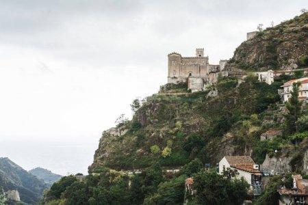 Foto de Savoca, Italia - 3 de octubre de 2019: Iglesia de San Nicolo en la colina cerca de árboles verdes y casas pequeñas en la colina. - Imagen libre de derechos