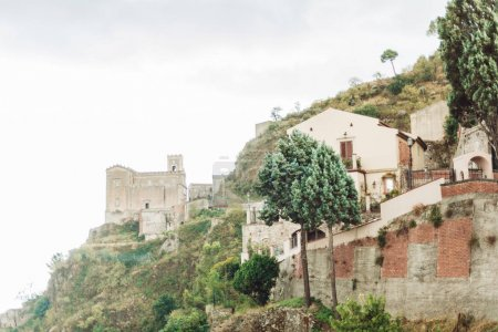 Photo for SAVOCA, ITALY - OCTOBER 3, 2019: Church of San Nicolo on hill near green trees and small houses - Royalty Free Image