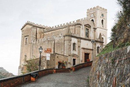 Foto de Savoca, Italia - 3 de octubre de 2019: Iglesia de San Nicolás cerca de pavimentar piedras en la carretera. - Imagen libre de derechos