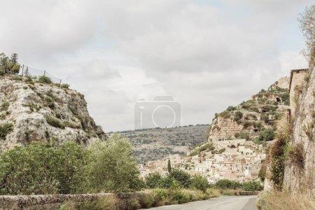 Photo pour Petites maisons près de la route et arbres verts sur les collines - image libre de droit