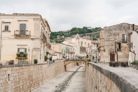 Photo pour Scicli, Italie - 3 octobre 2019 : street with paving stones on road near old church and buildings in scicli - image libre de droit