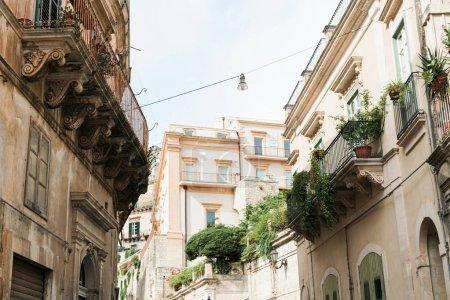 Photo pour Vue à faible angle des plantes sur les balcons de vieilles maisons de modica, Italie - image libre de droit