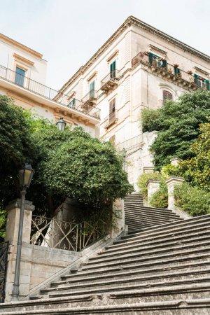 Photo pour Vue à faible angle des plantes et des arbres près des escaliers et des vieilles maisons de modica, Italie - image libre de droit