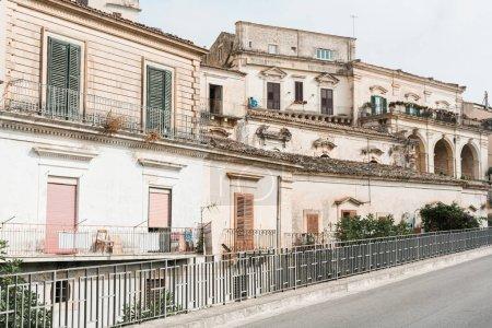 Photo pour Arbres verts près d'une clôture et vieux bâtiments à modica, Italie - image libre de droit