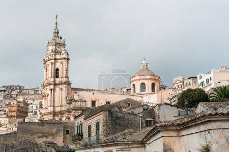 Photo pour Modica, Italie - 3 octobre 2019 : cathédrale baroque de san giorgio près de maisons contre ciel avec des nuages en sicile - image libre de droit