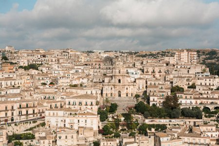 Photo for MODICA, ITALY - OCTOBER 3, 2019: baroque cathedral of san giorgio near old houses against sky with clouds - Royalty Free Image