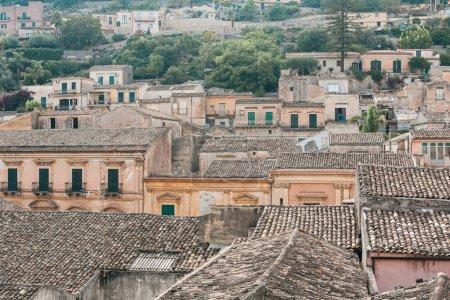 Photo pour Toits de maisons près d'arbres verts en ragusa, italiques - image libre de droit