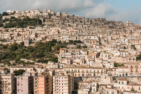 Photo for Sunlight on houses near green trees against sky with clouds in ragusa, italy - Royalty Free Image