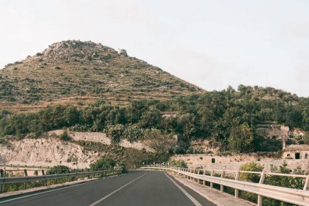 asphalt road near green trees on hill in ragusa, italy