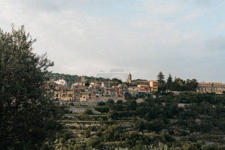 Photo pour Arbres verts près des maisons contre le ciel avec des nuages en ragusa, en italie - image libre de droit
