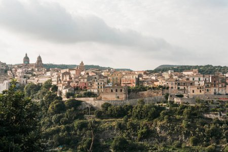 Photo for Green trees near small houses against sky with clouds in ragusa, italy - Royalty Free Image