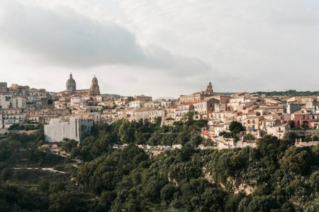 Photo for Sunlight on green trees near small houses against sky with clouds in ragusa, italy - Royalty Free Image