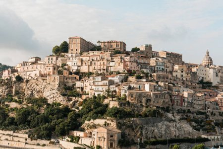 Photo for Sunshine on trees near small houses in ragusa, italy - Royalty Free Image
