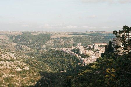 Photo pour La concentration sélective d'arbres verts sur les collines et les petites maisons de ragusa, italiques - image libre de droit