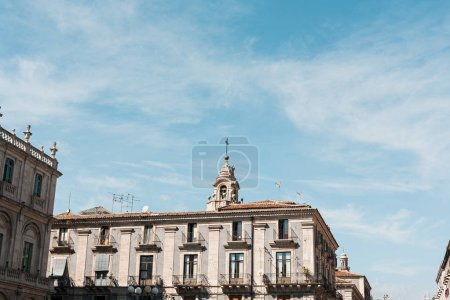 CATANIA, ITALY - OCTOBER 3, 2019: clock tower of Saint Agatha cathedral near old buildings
