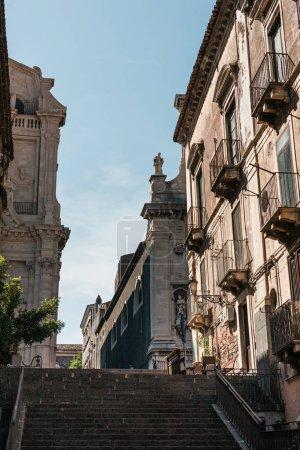 Photo pour Catane, Italie - 3 octobre 2019 : vue à angle bas de la façade de la cathédrale de Catane près des escaliers et des maisons - image libre de droit