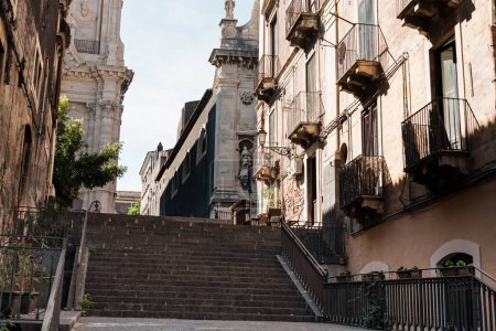Photo for CATANIA, ITALY - OCTOBER 3, 2019: low angle view of facade of catania cathedral near stairs and houses with balconies - Royalty Free Image