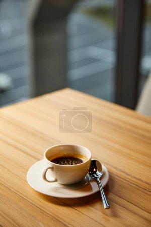 Foto de Enfoque selectivo de la taza con café cerca de la cuchara en la mesa de madera en la cafetería. - Imagen libre de derechos