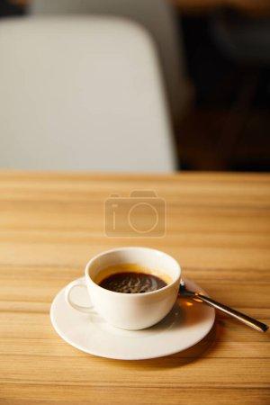 Photo pour Focalisation sélective de la tasse avec le café près de la cuillère dans le café - image libre de droit