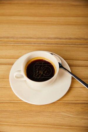 Photo pour Top vue de la tasse blanche avec café près de la cuillère dans le café - image libre de droit