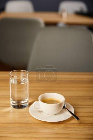 Photo pour Focalisation sélective de la tasse de café chaud près du verre avec de l'eau froide dans le café - image libre de droit