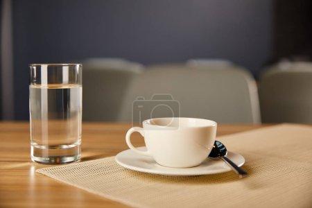 Photo pour Focalisation sélective de la tasse de café près du verre avec de l'eau dans le café - image libre de droit