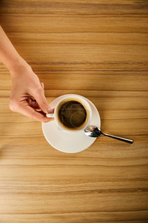 Photo for Top view of woman holding cup of coffee in cafe - Royalty Free Image