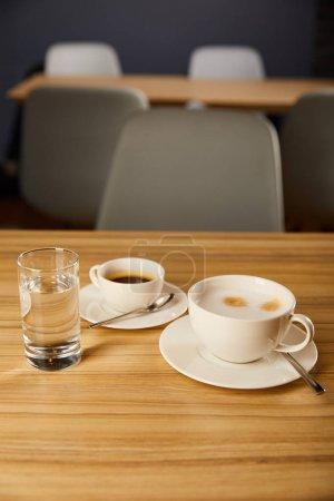 Photo pour Mise au point sélective de tasses à café près d'un verre d'eau dans un café - image libre de droit