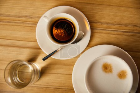 Photo for Top view of cups with coffee near glass of water in cafe - Royalty Free Image