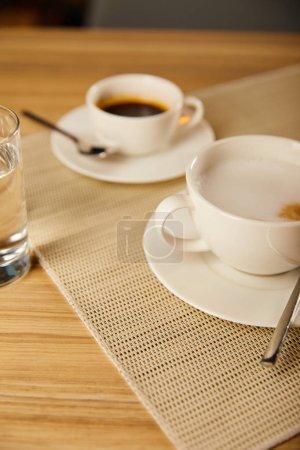 foyer sélectif de café chaud dans des tasses près du verre d'eau