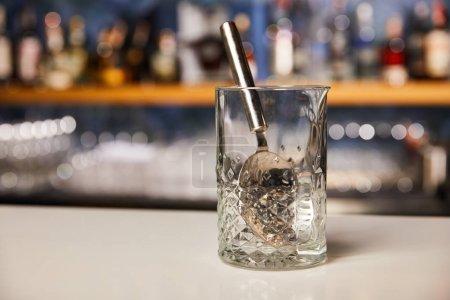 Photo pour Cuillère argent en verre vide sur pied de bar - image libre de droit