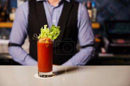 Photo pour Vue recadrée du barman près d'un cocktail Mary ensanglanté avec céleri et crevettes en verre - image libre de droit
