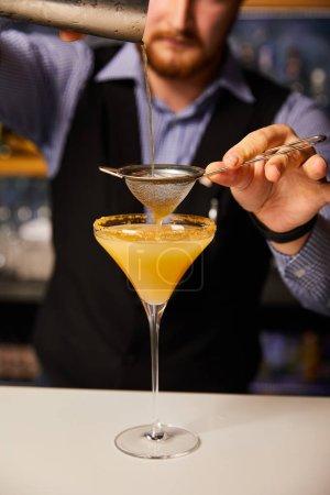Photo pour Vue en coupe du barman verser le cocktail en tenant un agitateur près du tamis et du verre de margarita - image libre de droit
