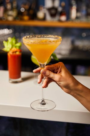 selective focus of woman holding margarita glass with cocktail