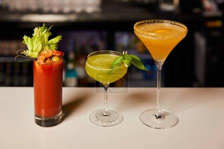 Photo pour Cocktails mélangés et frais dans des verres sur le comptoir du bar - image libre de droit