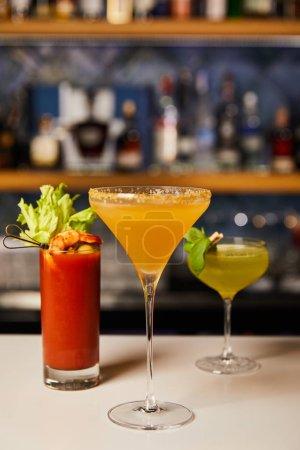 Photo pour Mise au point sélective de cocktails mélangés et frais dans des verres sur le comptoir du bar - image libre de droit