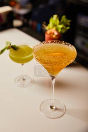 Photo pour Mise au point sélective de cocktails mixtes dans des verres sur le comptoir du bar - image libre de droit