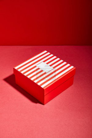 Photo for Striped red gift box on red background - Royalty Free Image