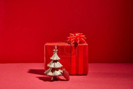 Foto de Caja de regalo roja y árbol decorativo de Navidad dorado con bauble en fondo rojo. - Imagen libre de derechos