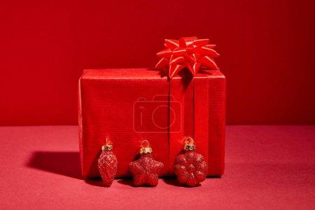 Photo pour Boîte cadeau de fête enveloppée de rouge avec baubles sur fond rouge - image libre de droit