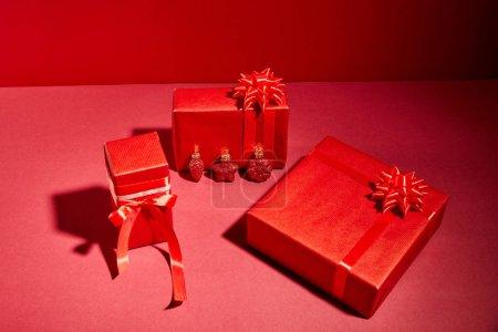 Photo pour Boîtes cadeaux de fête enveloppées de rouge avec rubans et arcs sur fond rouge - image libre de droit
