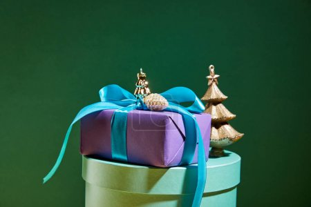 Photo for Gift box with golden Christmas decoration on green background - Royalty Free Image