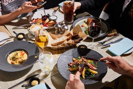 abgeschnittene Ansicht von Menschen, die leckeres Essen im Restaurant essen