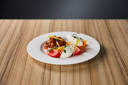 delicious restaurant dish with eggplant caviar and tomatoes on wooden table isolated on grey
