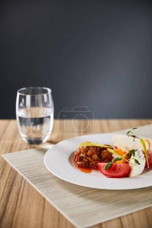 Photo pour Menu sélectif de délicieux plats de restaurant avec du caviar d'aubergine et des tomates servis sur une table en bois avec de l'eau isolée sur grise - image libre de droit