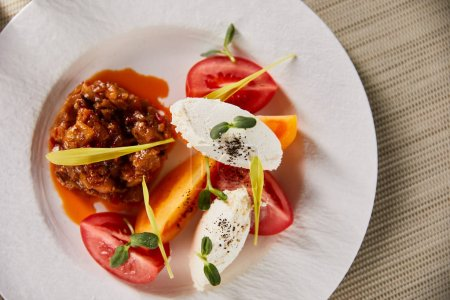 top view of delicious restaurant dish with eggplant caviar and tomatoes