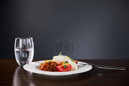 Photo for Delicious restaurant dish with eggplant caviar and tomatoes served on wooden table with water and cutlery on black background - Royalty Free Image