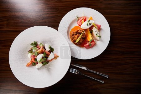 Photo for Top view of delicious restaurant dish with eggplant caviar and tomatoes and salad on wooden table with fork and knife - Royalty Free Image
